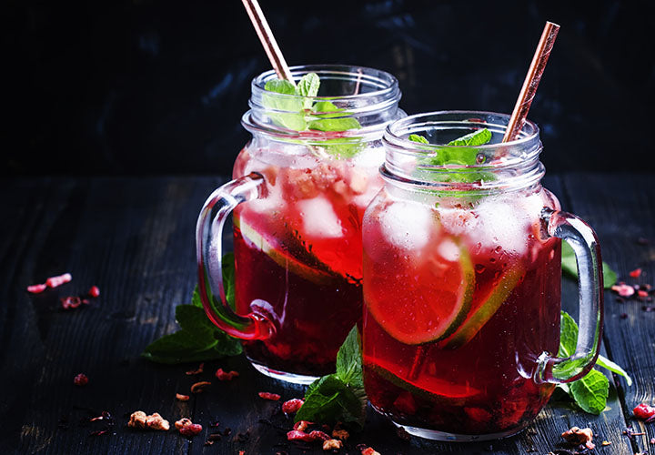 Mason jar mug filled with fizzy hibiscus drink with lime juice and fresh mint.