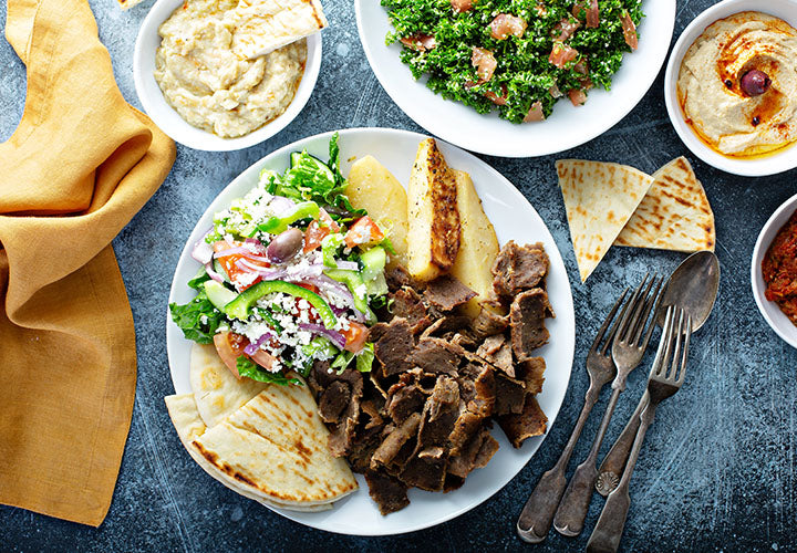 Picture of delicious gyro meat on a place with salad and pita bread.
