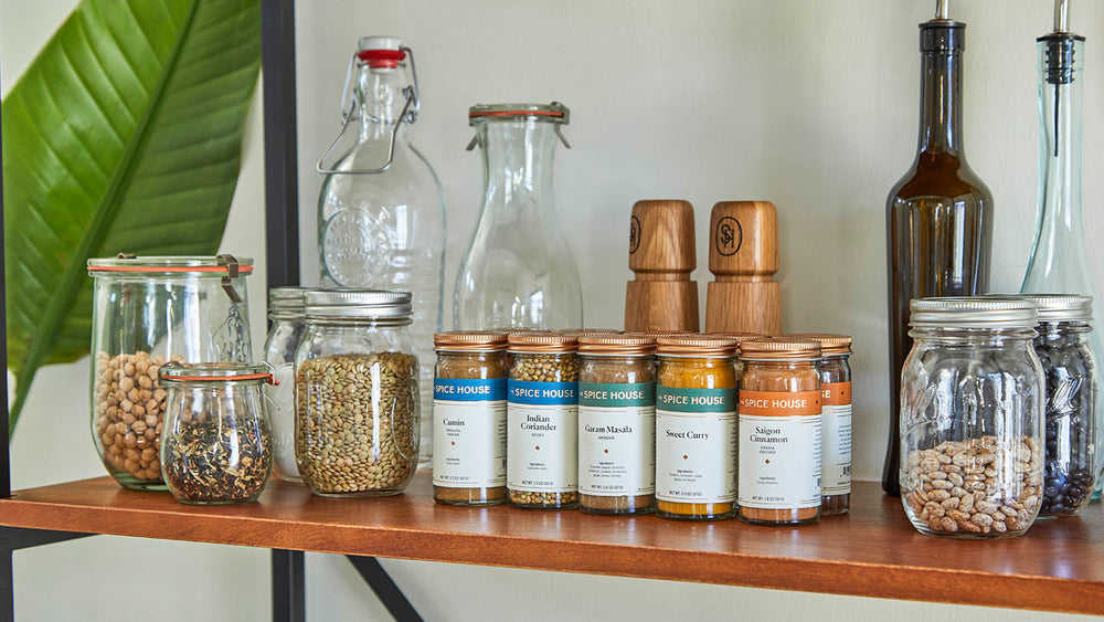 Spices in jars next to pantry staple ingredients