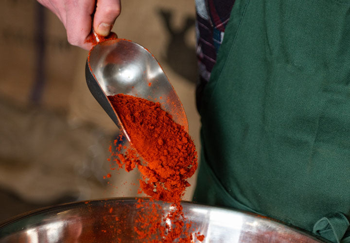 A large spoonful of gorgeous Hungarian sweet Paprika pouring into a bowl.