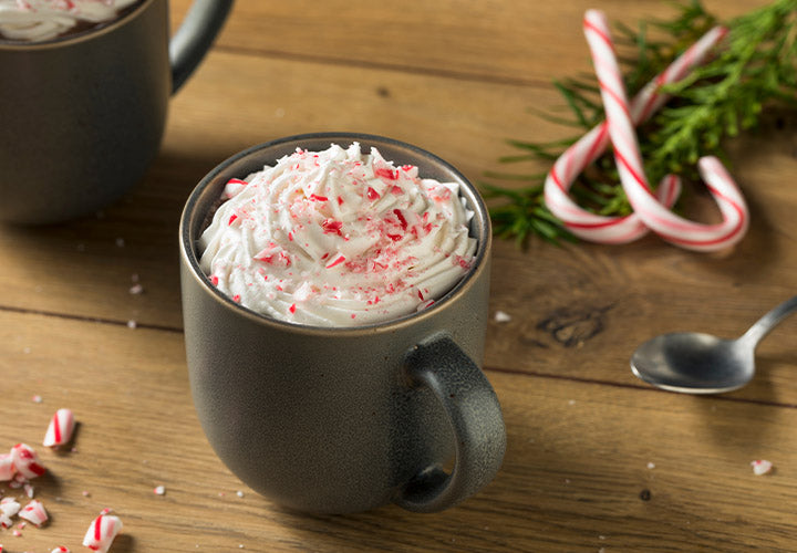 Hot cocoa made with peppermint extract and whipped cream and candy canes.