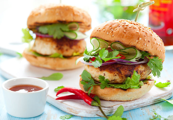 Spiced turkey burgers served on a sesame bun with lettuce, cilantro, onions, and cucumber.