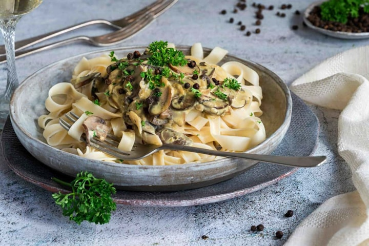 Porcini Mushrooms with Cream and Parmesan topping a bed of pasta