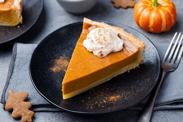 Slice of pumpkin pie with whipped cream and pumpkin spice garnish