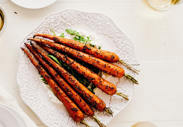 Spice roasted carrots are topped with fragrant coriander, anise, and caraway seeds then served over fresh ricotta with arugula.