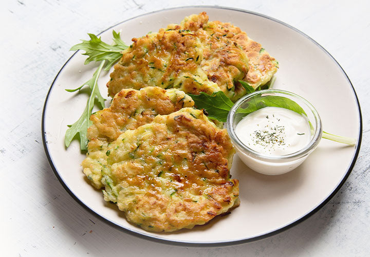 Zucchini pancakes served with onion sour cream dip.