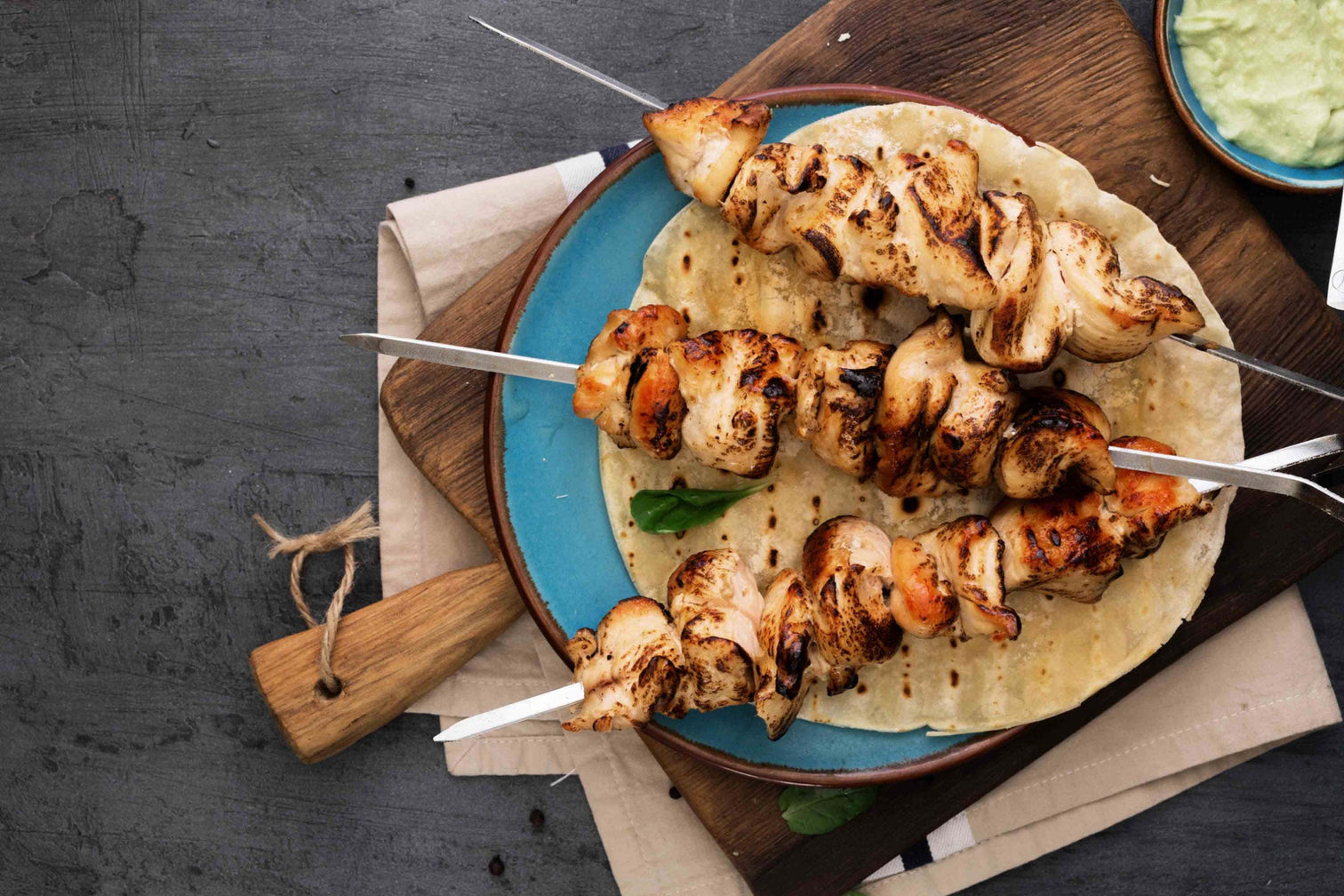 Grilled chicken skewers with piquant spices served on flatbread