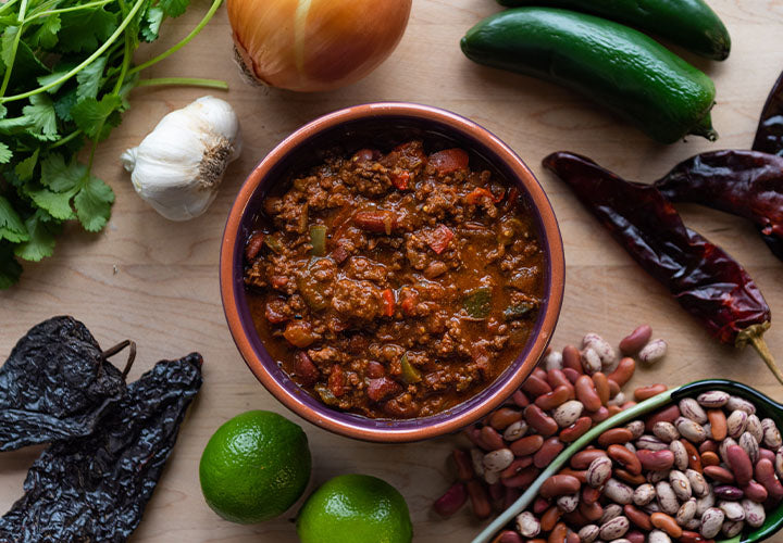 A bowl of homemade chili with all the ingredients laid out around it.