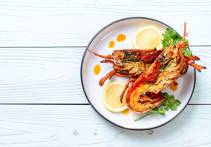 lobster on a plate with lemon, parsley, and garlic butter. Yummy!