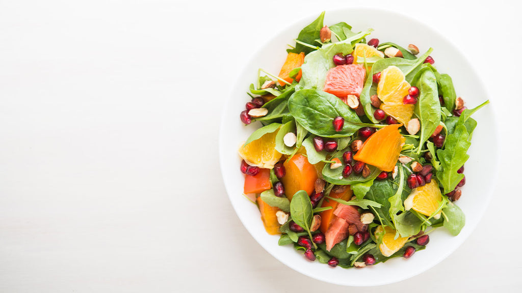 Crisp summery salad with pomegranate seeds, citrus, and persimmon.