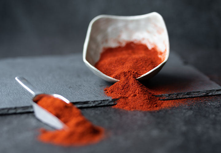 Fresh paprika spice in a bowl and spoon