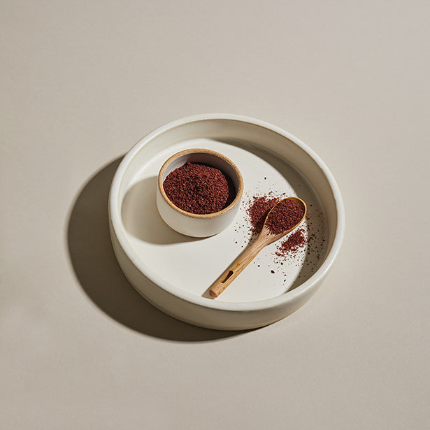 Sumac spice in a bowl with wooden spoon and plate.