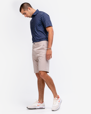 Navy blue breathable polo with orange and turquoise tribal print and peach inner collar paired with khaki shorts