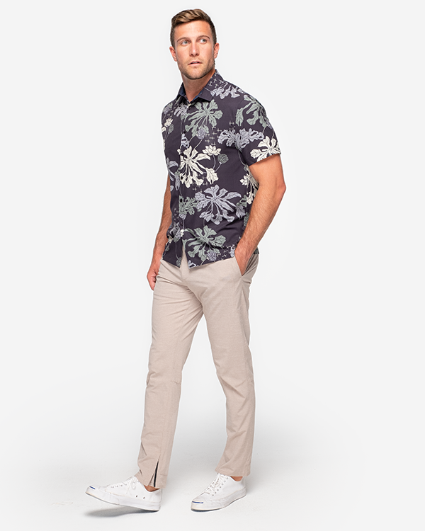 Black lightweight short sleeve button down with and allover off-white, olive green, and grey plant print paired with khaki pants