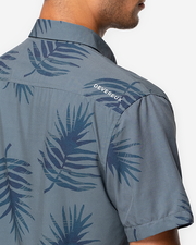 "Green-Blue lightweight short sleeve button down with navy blue allover palm print with ""devereux"" logo on right shoulder"