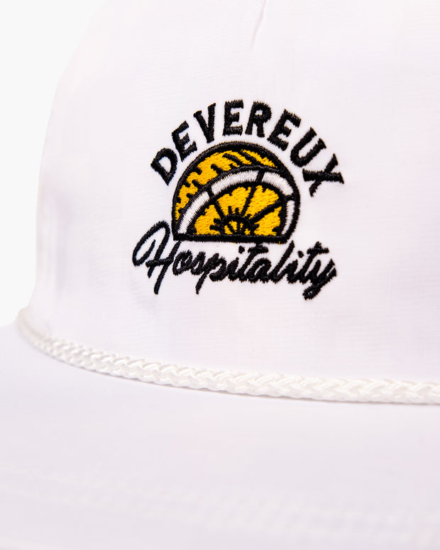 "White flat brim hat with black and yellow embroidered lemon ""Devereux"" and srcipt ""Hospitality"" graphic featuring white woven rope on base of front panel"