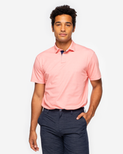 Orange pink coral golf performance polo with navy blue collar detail and two button placket paired with dark grey shorts