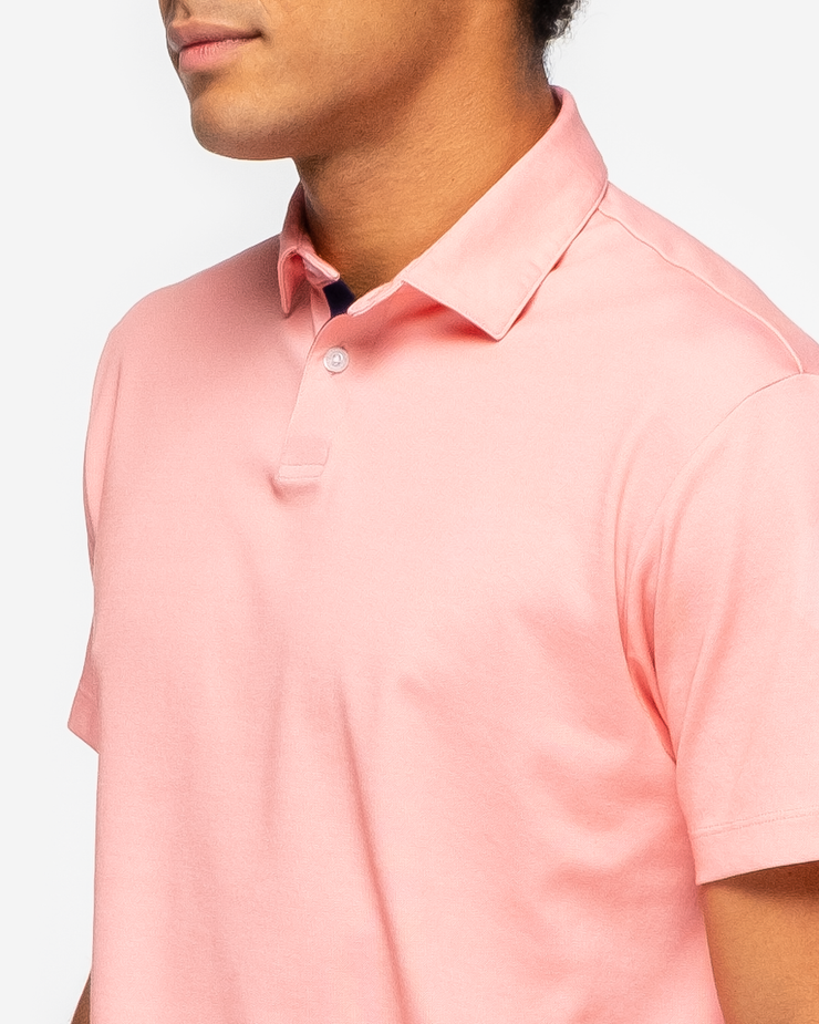 Orange pink coral golf performance polo with navy blue collar detail and two button placket p