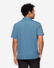 Dark and light blue performance polo with light blue geometric print and peach inner collar paired with black shorts