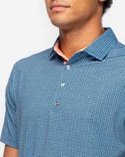 Dark and light blue performance polo with light blue geometric print and peach inner collar with four silver button placket