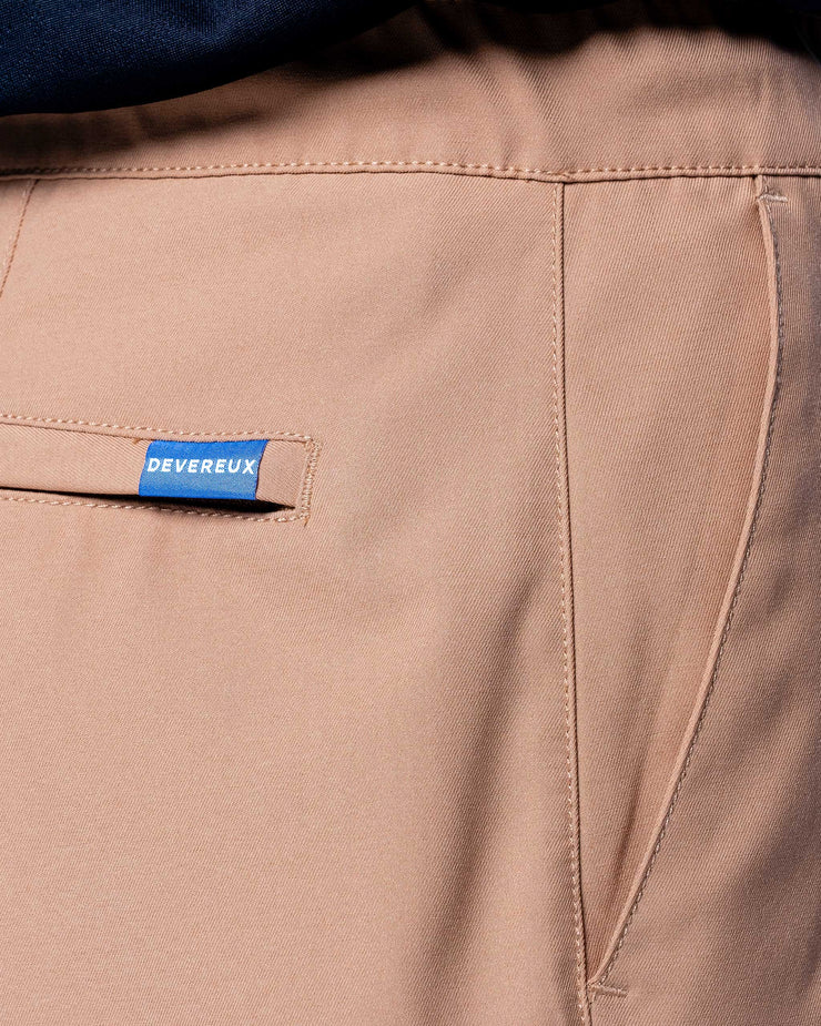 "Rusted tan active short with black drawstrings elastic wasteband and blue ""devereux"" tag on back pocket"