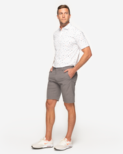 "White breathable polo with mini ""palm tree palm leaf and pineapple"" all over print and peach inner collar detail paired with grey shorts"