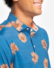 Heathered bright blue breathable polo with medium sized peach hawaiaan floral all over pattern and peach inner collar detail
