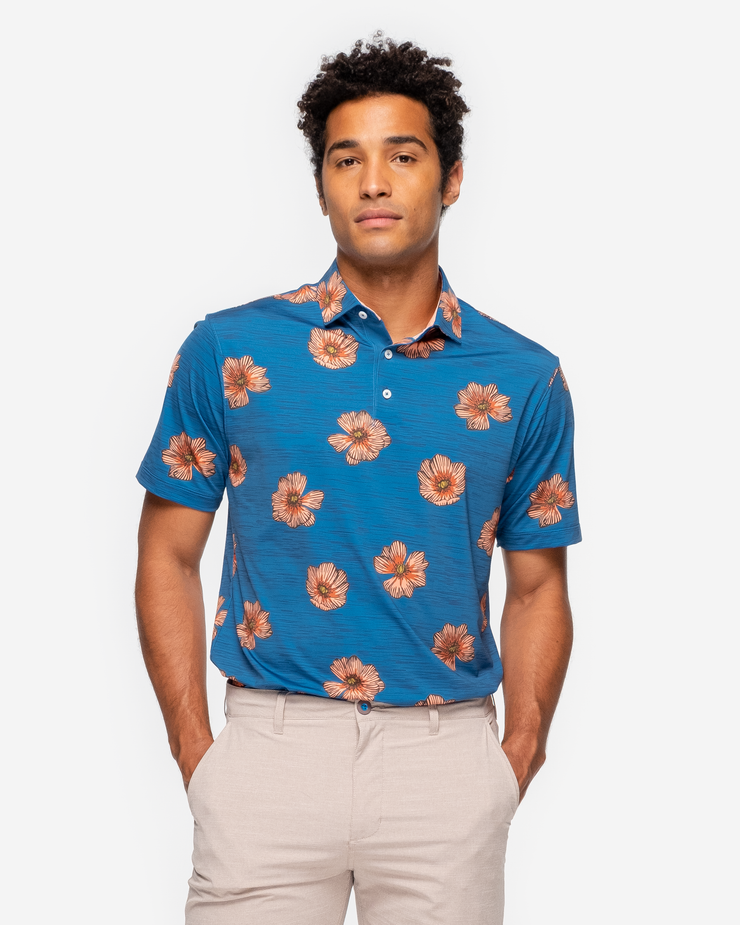 Heathered bright blue breathable polo with medium sized peach hawaiaan floral all over pattern and peach inner collar