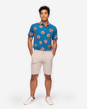 Heathered bright blue breathable polo with medium sized peach hawaiaan floral all over pattern and peach inner collar paired with khaki shorts