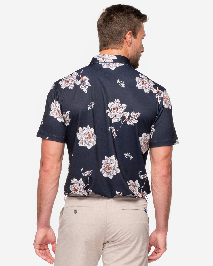 Black breathable polo with white and orange floral print and peach orange inner collar with khaki shorts