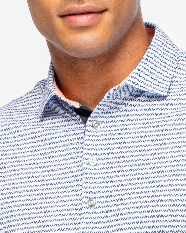 White sweat wicking polo with navy blue V shape all over pattern and peach inner collar with four button placket