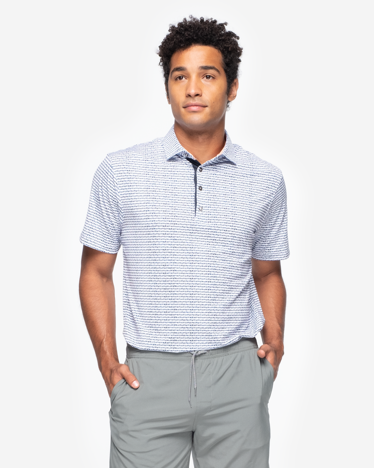 White sweat wicking polo with navy blue V shape all over pattern and peach inner collar and four button placket paired with grey shorts
