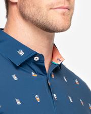 Navy blue sweat wicking polo with orange whiskey cocktail all over pattern and peach inner collar
