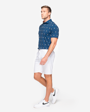 Navy blue sweat wicking polo with orange whiskey cocktail all over pattern and peach inner collar paired with white shorts
