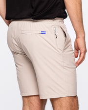 "Khaki active short with black and white zig zag drawstring and zipper pocket and blue ""devereux"" tag on back pocket"