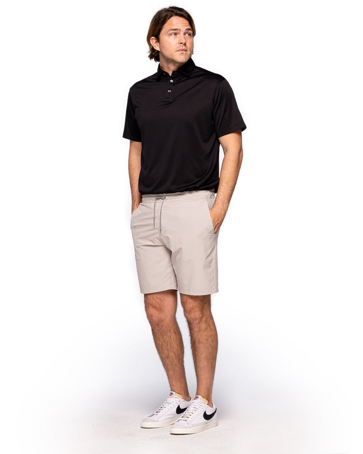 Khaki active short with black and white zig zag drawstring and zipper pocket paired with black polo