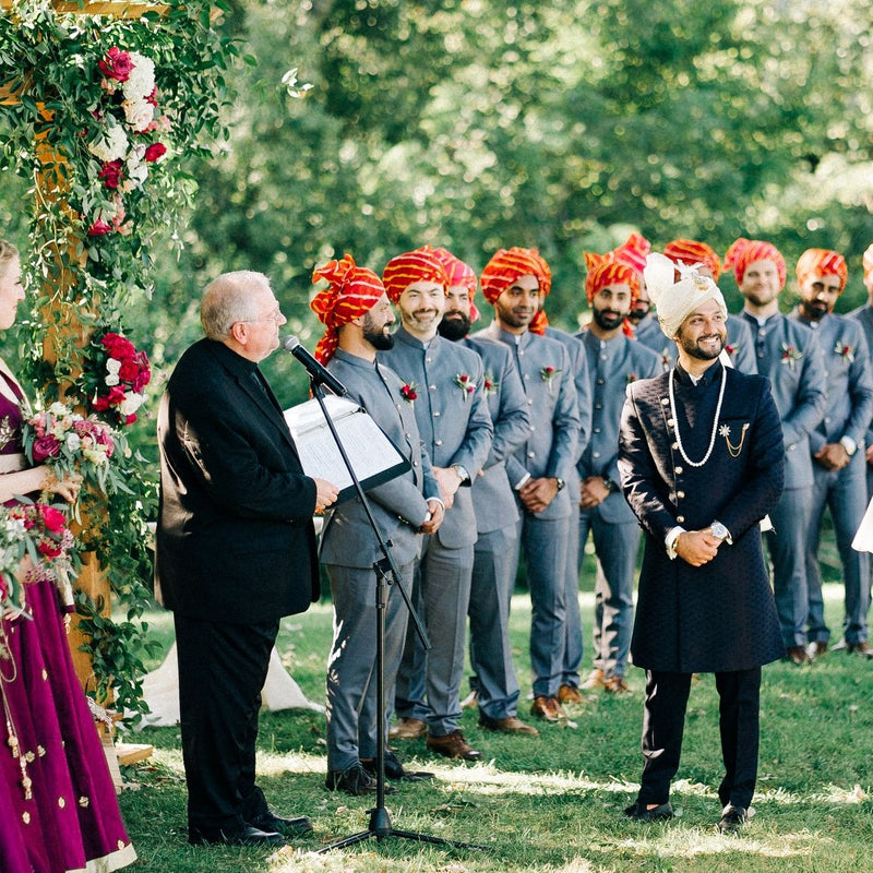Indian groom in a Sherwani with his groomsmen in bandhgalas waiting for his bride to arrive down the aisle