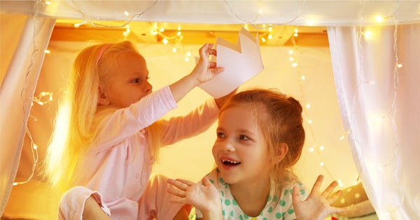 Imagination and creativity-girls playing under a make-believe tent with lights