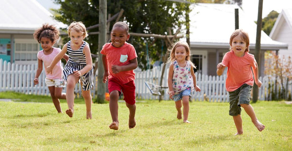benefits of play-importance of play-unstructured play-five preschoolers running freely in the grass