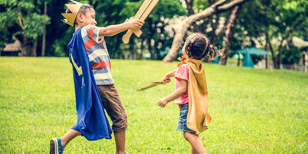 best gift for kids-give the gift of play-siblings enjoying a pretend play sword fight