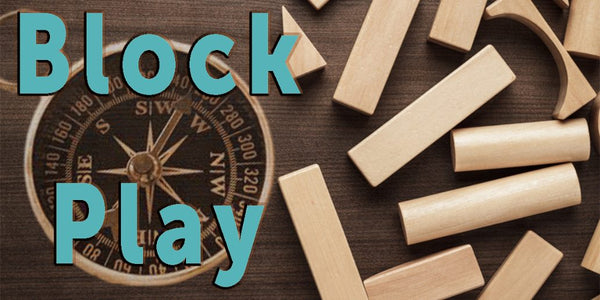 block play-benefits of blocks play-wooden blocks scattered on a wood floor with a compass