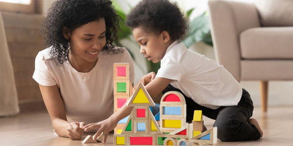 cognitive development in toddlers-mother and toddler son are on the floor engaged in block play