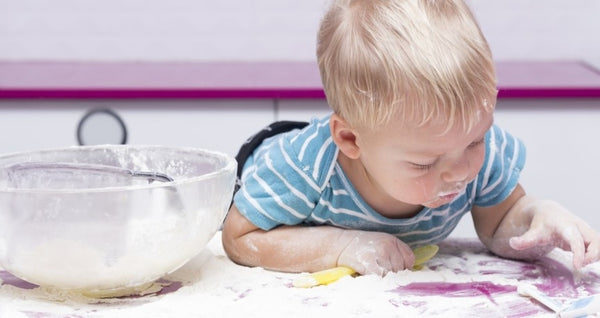 exploratory play-little boy playing in spilled flour