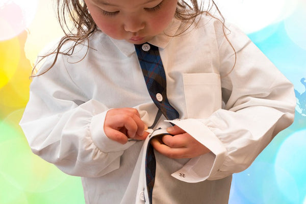 Fine motor development- young girl working to button her shirt independently
