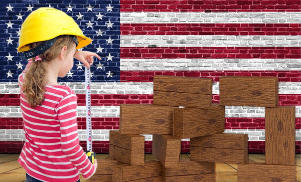 giant building blocks-timber blocks-made in america- girl wearing a hardhat, with measuring tape, with a US flag background