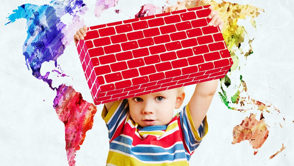 gross motor development-jumbo blocks-greater independence-toddler confidently holding up a giant building block