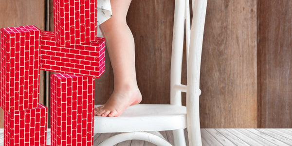 jumbo blocks-build it big-take building to new heights-little girl standing on a chair stacking giant red blocks