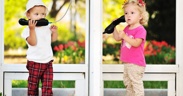 language activities for preschooler-language development-two young girls having a phone conversation outside