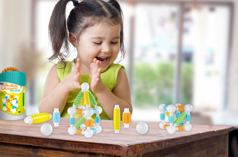 magnetic blocks-toddler girl enjoying her grippies builders on a large wooden table