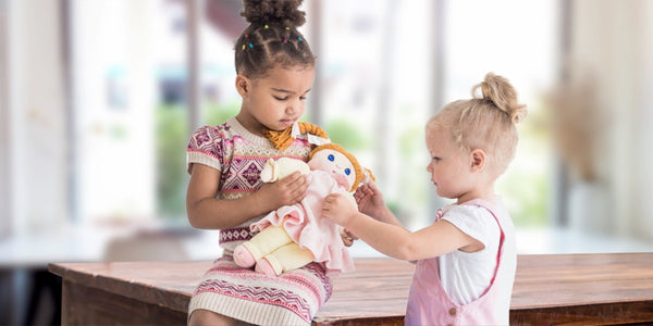 social-emotional activities for preschoolers-two young girls caring for a doll